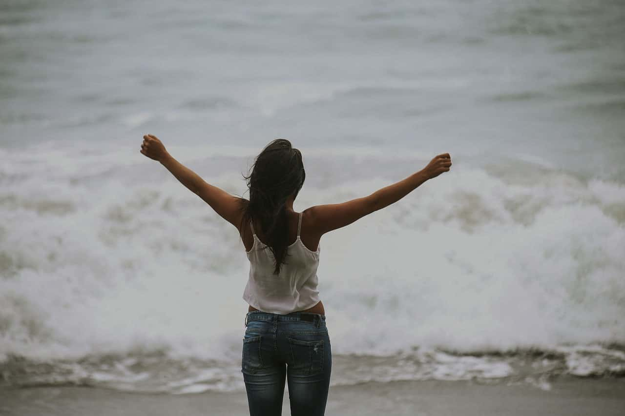 a woman raising her arms up facing the sea