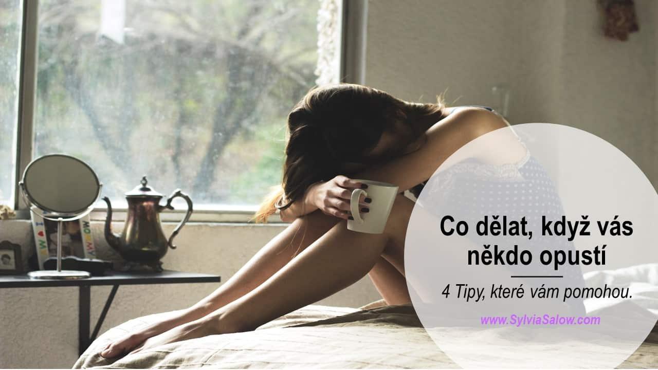 žena sedící na posteli s hlavou v klíně a s hrníčkem kávy v ruce