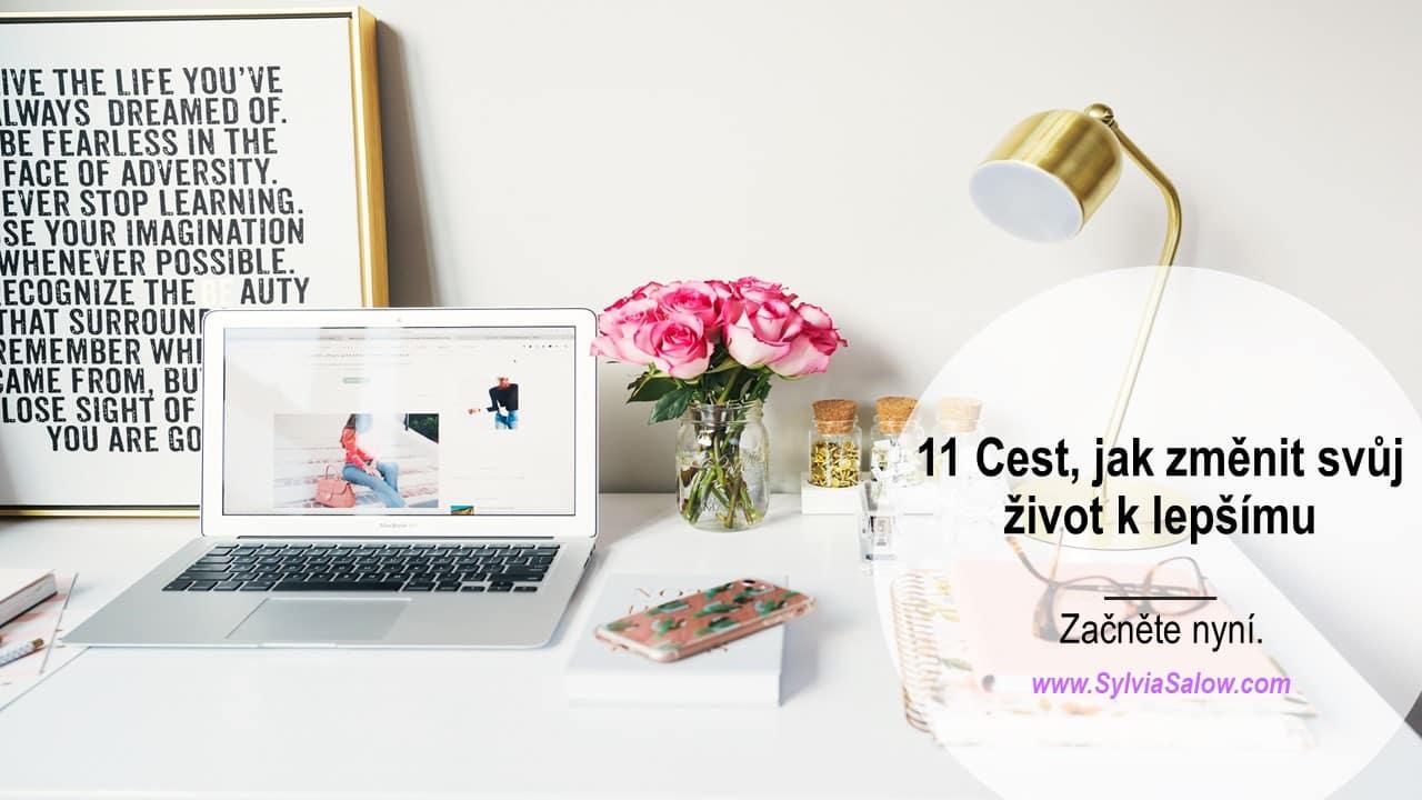 počítač, váza s růžemi a pracovní stůl