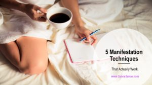 woman sitting on bed writing down into a journal and drinking a cup of coffee